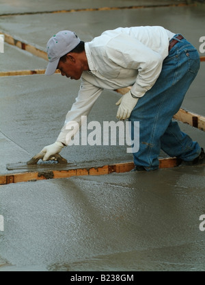 Workman leveling wet concrete with a Darby during construction of a patio in the backyard of a private home in California - Stock Photo