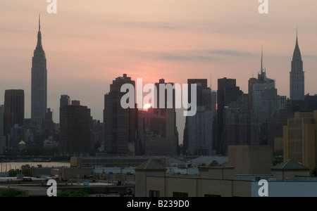 New York City Cityscape at sunset. Empire State Building on the left, Chrysler Building on the right. - Stock Photo