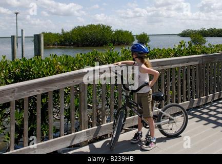 A girl looking at an osprey nest on a biking trip through J N Ding Darling National Wldlife Refuge Sanibel Island - Stock Photo