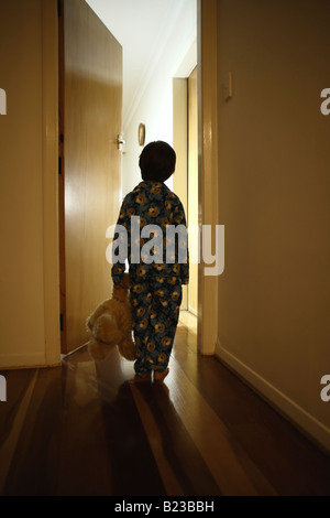 Six year old boy stands in corridor in pyjamas with teddy bear - Stock Photo