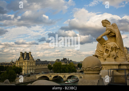 Statue on roof of Musee D'Orsay with dramatic sky background and elevated view of sightseeing boat on the river Seine by famous art Museum the Louvre