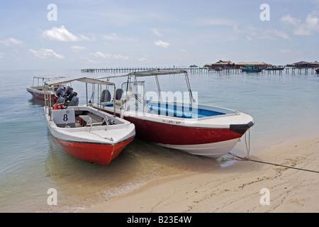 Borneo Divers boats pulled up on the beach at Mabul Island Resort nr Sipadan Sabah Malaysia - Stock Photo