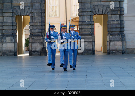 The changing of the guards at Prague Castle wearing light blue summer uniform and carrying rifles - Stock Photo