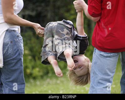 Little boy being spun around in the air by his parents - Stock Photo