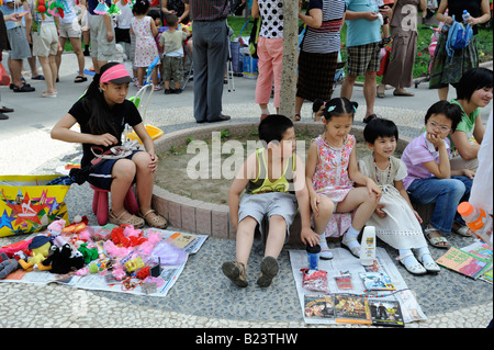 Teenages sell uesd goods at flea market on Sunday in a community in Beijing, China. 13-Jul-2008 - Stock Photo