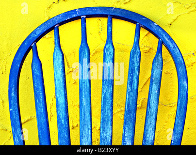 Old blue painted wooden chair leaning against a bright yellow stucco wall - Stock Photo