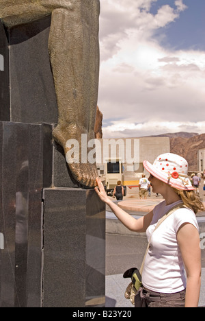 Caucasian Teen Girl Rubs Toes of Winged Figures of the Republic at Hoover Dam Nevada USA Stock Photo
