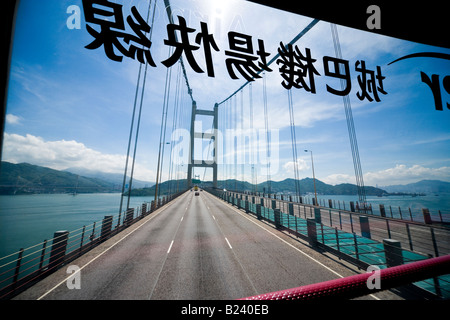 Hong Kong Tsing Ma Bridge seen through the windshield from the upper level of a double-decker bus - Stock Photo