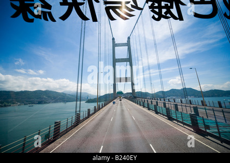 Hong Kong Tsing Ma Bridge seen through the windshield from the upper level of a double-decked bus - Stock Photo