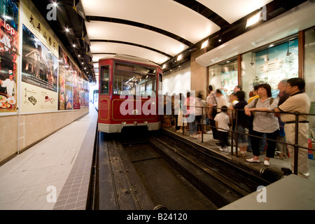 Passengers boarding the Victoria Peak Tram at its lower terminus station in Hong Kong, China SAR. - Stock Photo