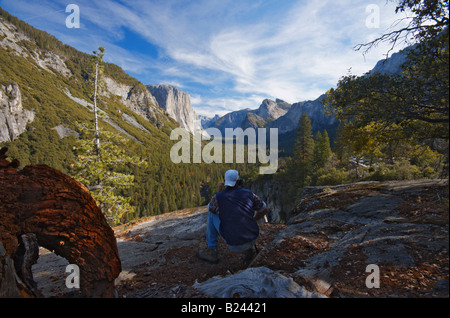 A man is photographing Yosemite Valley with Half Dome visible in the background - Stock Photo