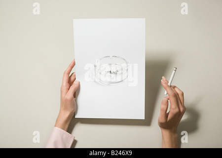 A woman holding a photograph of an ashtray and a cigarette - Stock Photo