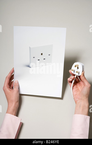 A woman holding a photograph of a socket and a plug - Stock Photo