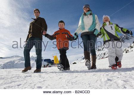A family walking through a ski resort - Stock Photo