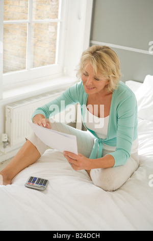 Woman with paper and calculator - Stock Photo