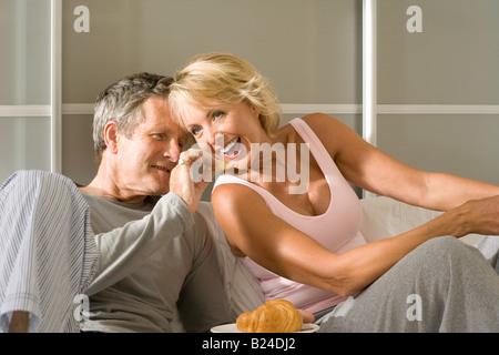 Couple sharing croissant - Stock Photo