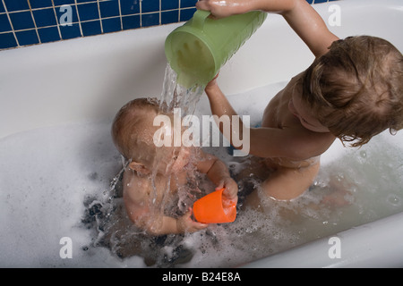 Boy pouring water over baby brother - Stock Photo