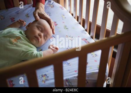 Baby in crib - Stock Photo