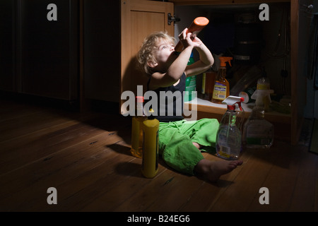Boy drinking cleaning product - Stock Photo