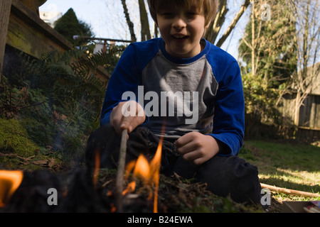 Boy playing with fire - Stock Photo
