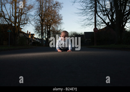 Baby crawling in road - Stock Photo