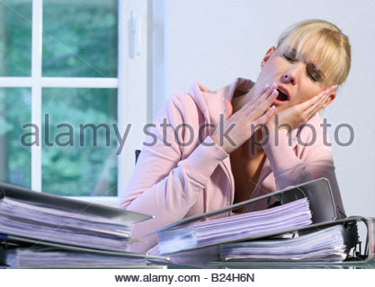 tired woman working in office - Stock Photo