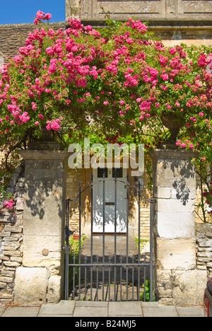 Pink rambler rose surmounting a metal gate and stone entrance to a personal property in England - Stock Photo