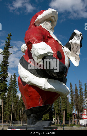 Statue of Father Christmas / Santa Claus standing besides his 'home'  in North Pole, Alaska. - Stock Photo