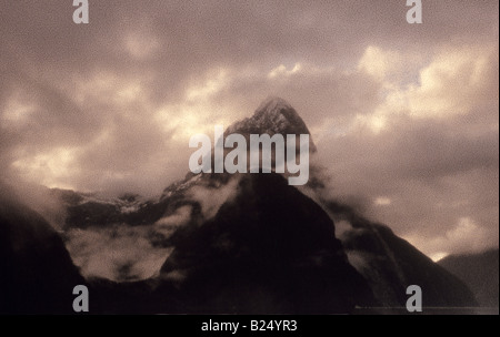 Milford Sound, Fiordland, New Zealand, shoreline view, with cloud and mist clearing over the iconic mountain Mitre - Stock Photo