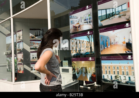Young first time buyer looking at expensive houses for sale in estate agent window in London England UK - Stock Photo