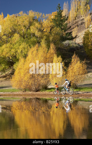 Mountain Bikers and Autumn Colours Bannockburn Inlet Lake Dunstan Central Otago South Island New Zealand - Stock Photo