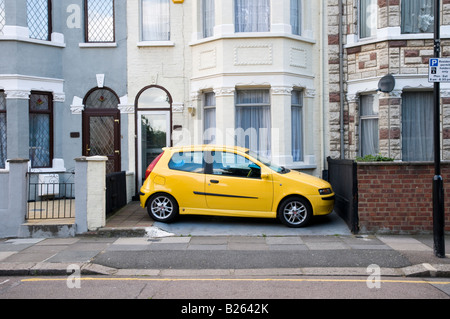 Car parked in front garden of terraced house, London, England, UK - Stock Photo