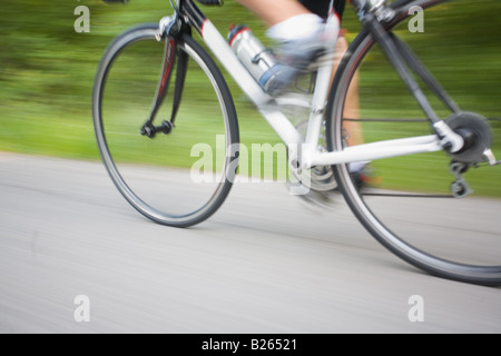 Blurred motion of a cyclist pedaling - Stock Photo