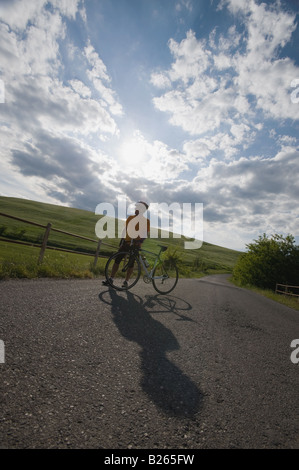Cyclist standing with bike on road beneath cloudy sky