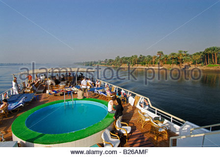 cruise on the Nile, view from upper deck to pool on deck and palm trees at western bank, Nile between Luxor and - Stock Photo
