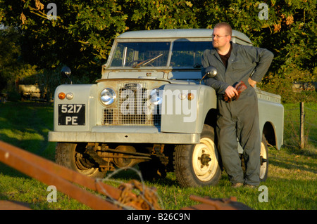 Workman in overall leaning  against a historic 1963 Landrover Series 2a truckcab in very original and full working - Stock Photo