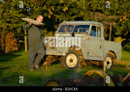 Workman loading a timber beam into a historic 1963 Landrover Series 2a truckcab in original and full working condition. - Stock Photo