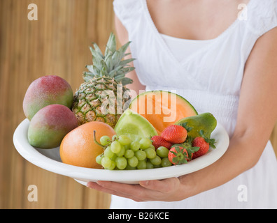 Woman holding plate of fruit - Stock Photo