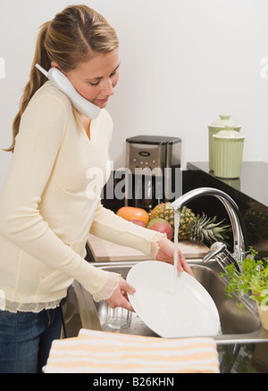 Woman washing dishes - Stock Photo