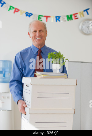 Retiring senior businessman carrying boxes - Stock Photo