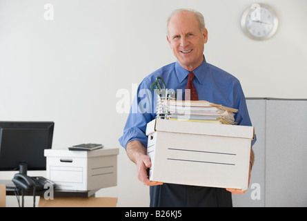 Senior businessman carrying box and office supplies - Stock Photo