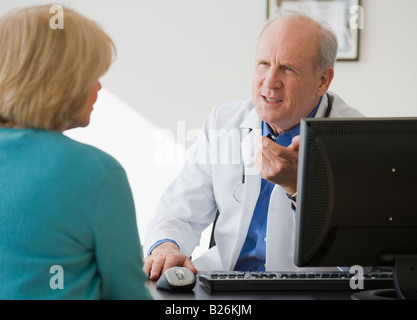Senior male doctor talking to patient - Stock Photo