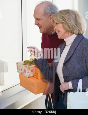 Senior couple holding gifts next to window - Stock Photo