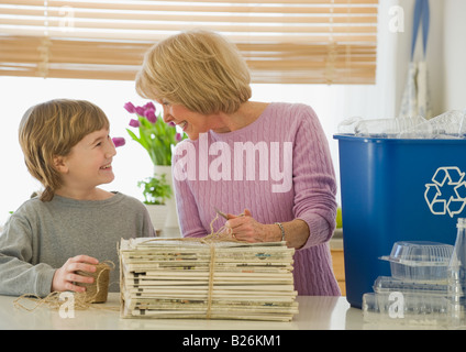 Grandmother and grandson recycling newspapers - Stock Photo