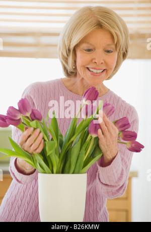 Senior woman arranging flowers - Stock Photo