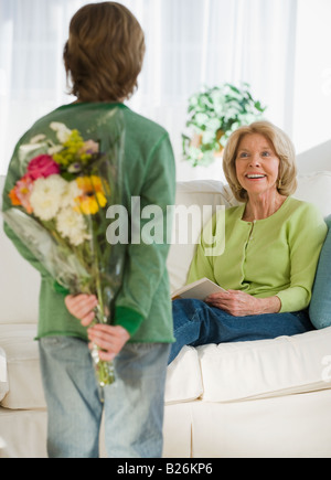 Grandson surprising grandmother with flowers - Stock Photo