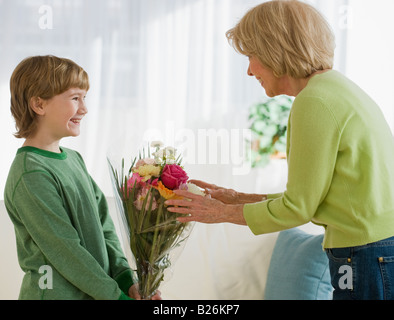 Grandson giving flowers to grandmother - Stock Photo