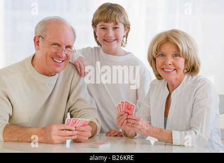 Grandson watching grandparents play cards - Stock Photo