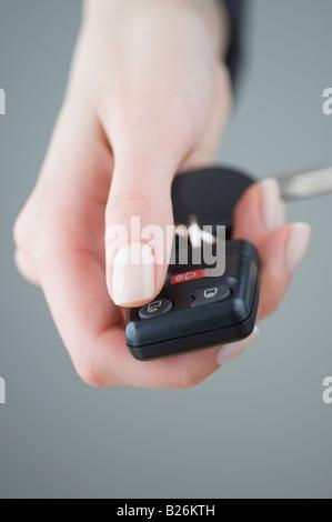 Woman pressing unlock button on keychain - Stock Photo