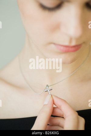Woman wearing cross necklace - Stock Photo
